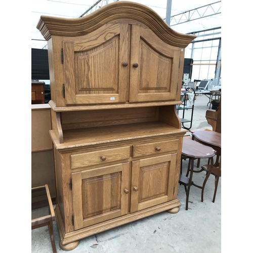 697 - AN OAK DRESSER WITH TWO LOWER DOORS AND DRAWERS AND TWO UPPER DOORS...