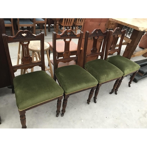 717 - FOUR CARVED MAHOGANY DINING CHAIRS ON CASTERS WITH GREEN VELVET EFFECT UPHOLSTERY...