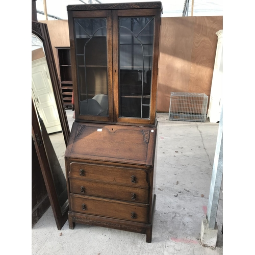 725 - AN OAK BUREAU BOOKCASE WITH FALL FRONT, THREE DRAWERS AND TWO UPPER GLAZED DOORS...