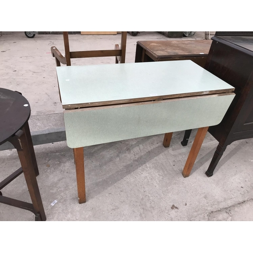 733 - A RETRO FORMICA TOPPED DROP LEAF KITCHEN TABLE...