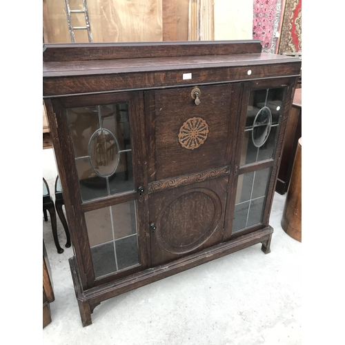 739 - AN OAK CABINET WITH FALL FRONT, CENTRE DOOR AND TWO GLAZED SIDE DOORS...