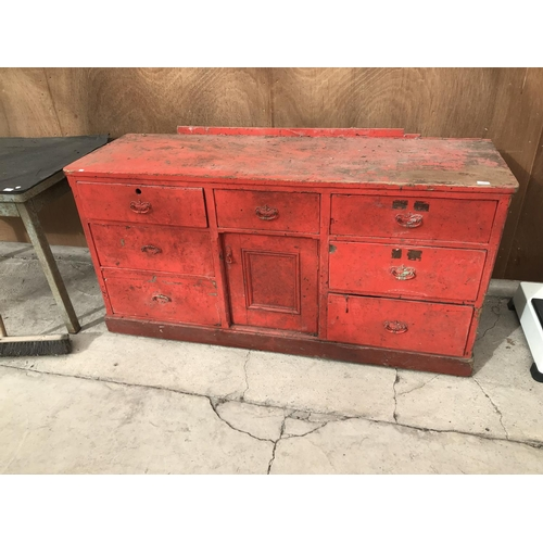 76 - A VINTAGE RED PAINTED SIDEBOARD WITH SEVEN DRAWERS AND ONE DOOR...