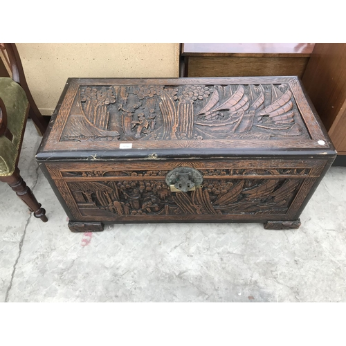 956 - A HEAVILY CARVED CAMPHOR WOOD BEDDING CHEST WITH BRASS LOCK AND ELABORATE ESCUTCHEON...