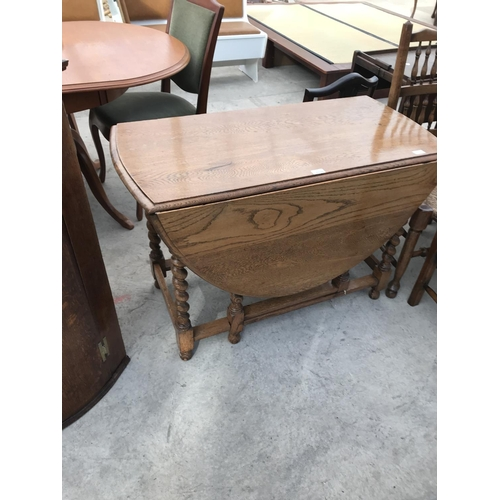 1015 - AN OVAL OAK DROP LEAF DINING TABLE ON BARLEY TWIST SUPPORTS...