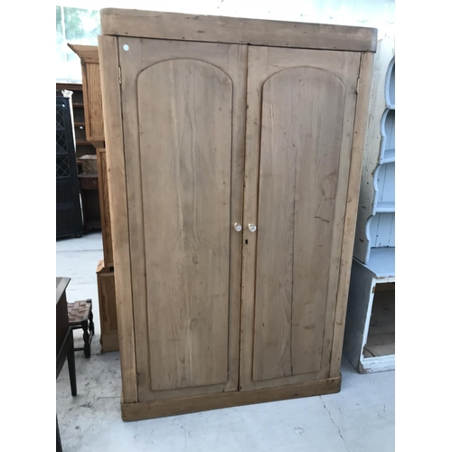 1051 - A PITCH PINE TWO DOOR WARDROBE WITH INNER DRAWER...