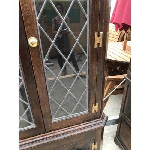 1079 - AN OLD CHARM STYLE OAK CORNER CUPBOARD WITH TWO LOWER AND TWO UPPER GLAZED DOORS AND BRASS H HINGES...