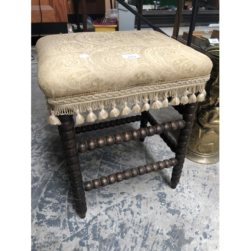 407 - AN UPHOLSTERED BOBBING STOOL WITH ROUND BEADED SUPPORTS...