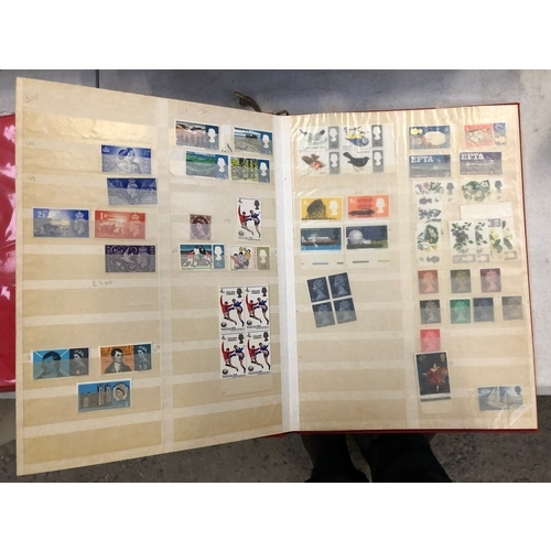 419 - A SELECTION OF GB UNMOUNTED MINT DECIMAL STAMPS HOUSED IN A RED STOCK BOOK, FACE VALUE OF £100+...