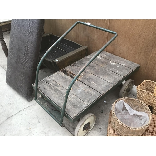 22 - A VINTAGE FOUR WHEELED WOODEN TRUCK WITH METAL WHEELS...