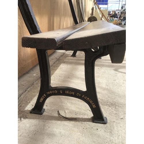 16 - A WOODEN BENCH WITH CAST IRON BENCH ENDS DETAILED WITH 'UNITY WOOD & IRON CO PADIHAM' 157CM LONG...
