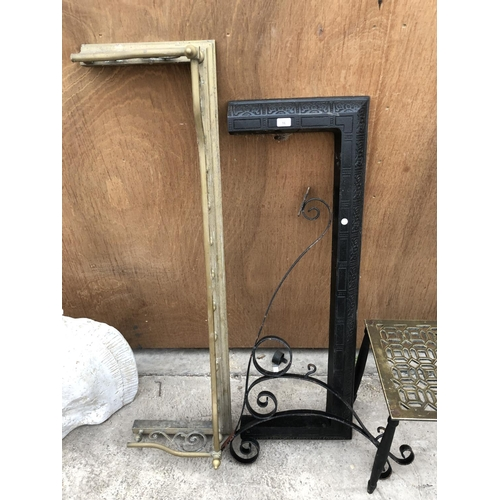 16 - A BLACK FIRE FENDER AND AN ORNATE WROUGHT IRON SIGN BRACKET...