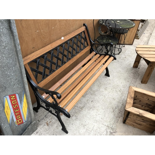 32 - A WOODEN GARDEN BENCH WITH CAST SLATTED BACK AND ENDS...