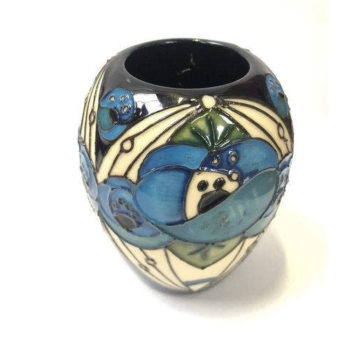 589 - A SMALL MOORCROFT RED ROSE BLUE VASE...