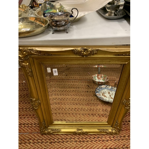 135 - A BEVELLED MIRROR WITH A GILDED FRAME...