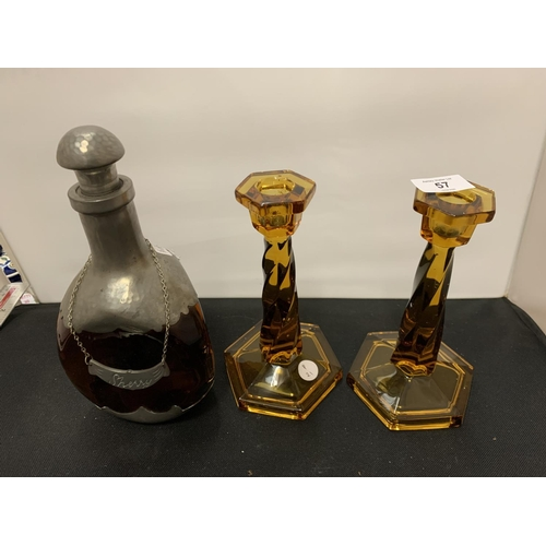 57 - A PEWTER AND GLASS SHERRY BOTTLE WITH STOPPER AND NAME CHAIN AND TWO AMBER COLOURED GLASS CANDLESTIC...