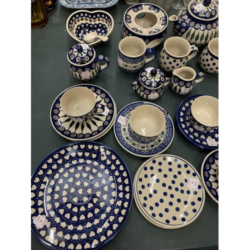 69 - A THIRTY PIECE COLLECTION OF HAND-MADE BOLESLAWIEC POTTERY...