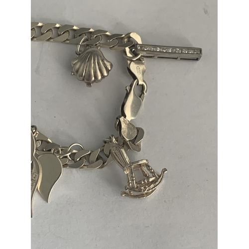 545 - A SILVER CHARM BRACELET WITH EIGHT CHARMS...