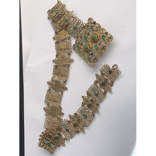 576 - A YELLOW METAL BELT WITH GREEN STONES...