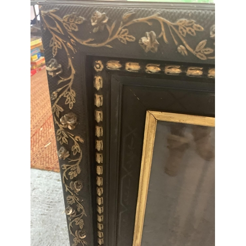 165 - A LARGE ORNATE GILT AND BLACK FRAME CONTAINING A PICTURE OF A VICTORIAN WOMAN...