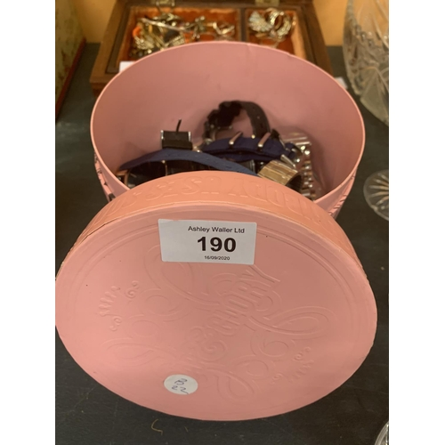 190 - A CIRCULAR PINK BOX CONTAINING A LARGE QUANTITY OF WRISTWATCHES (APPROX 40)...