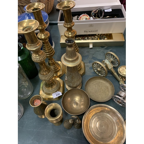 234 - AN ASSORTMENT OF BRASSWARE TO INCLUDE THREE LARGE CANDLE STICKS...