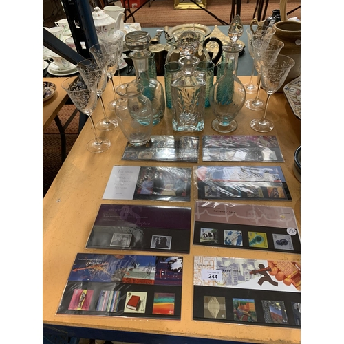 244 - A QUANTITY OF GLASSWARE TO INCLUDE THREE DECANTERS AND A SELECTION OF MILLENIUM EDITION STAMPS...