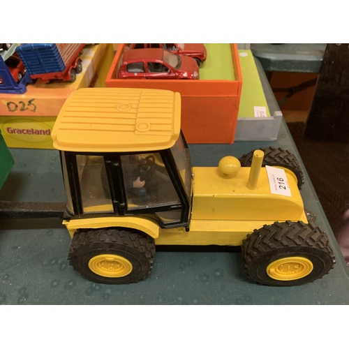 216 - A YELLOW WOODEN TRACTOR WITH PLASTIC CAB, WOODEN TRAILER, FLAT ROLLER AND A WOODEN LAND ROVER DEFEND...