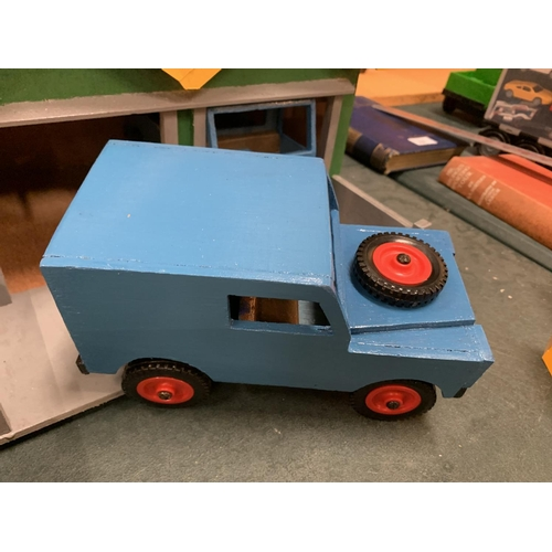 230 - A HANDMADE WOODEN VEHICLE BUILDING COMPLETE WITH A WOODEN LORRY AND A WOODEN LAND ROVER...