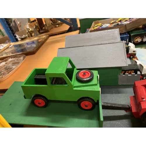 239 - A WOODEN TRACTOR TOWING A TRAILER WITH A WOODEN LAND ROVER...