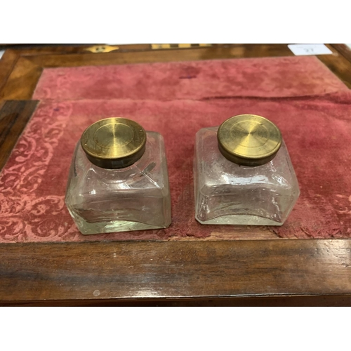 27 - A VINTAGE WOODEN WRITING SLOPE WITH BRASS DETAIL TO INCLUDE A PAIR OF GLASS INK WELLS AND A KEY