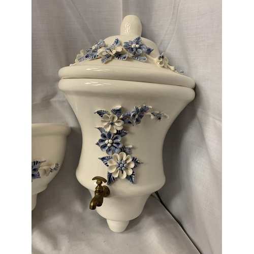 18 - A PAIR OF CERAMIC WALL MOUNTED WATER VESSEL AND BOWLWITH DECORATIVE BLUE AND WHITE FLOWERS IN RELIEF...