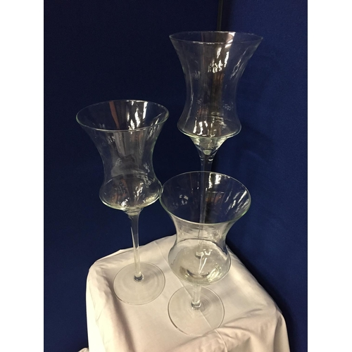 12 - THREE LARGE GLASS CANDLE HOLDERS APPROXIMATE HEIGHTS 70CM 55CM 40CM
