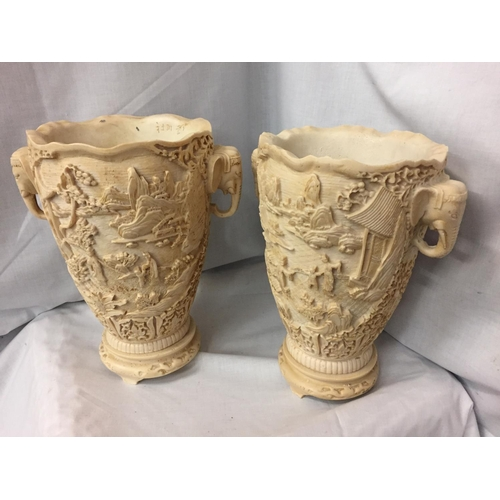 19 - A PAIR OF HEAVILY CARVED ORIENTAL VASES WITH ELEPHANT DESIGN TWIN HANDLES 30CM HIGH