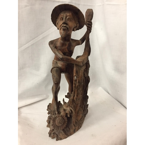 32 - AN INTRICATELY CARVED AFRICAN TRIBAL FIGURE OF A FISHERMAN CASTING HIS NET, HEIGHT 42 CM