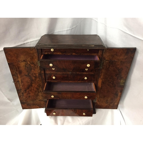 44 - A WALNUT MINATURE CABINET TO INCORPORATE SEVEN DRAWERS 44CM HIGH POSSIBLY A WATCH MAKERS CABINET