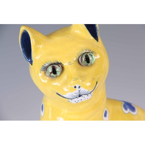 40 - AN EARLY 20th CENTURY GALLE STYLE FAIENCE CAT having a yellow glaze with blue heart decoration and g...