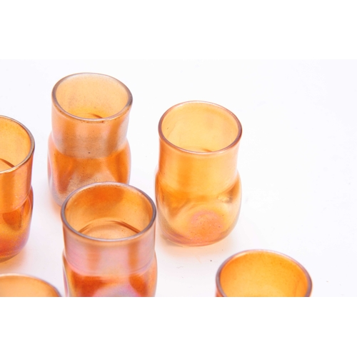 15 - A SET OF TEN TIFFANY FAVRILE SHOT GLASSES with square dimple bodies and plain necks 5cm high - signe...