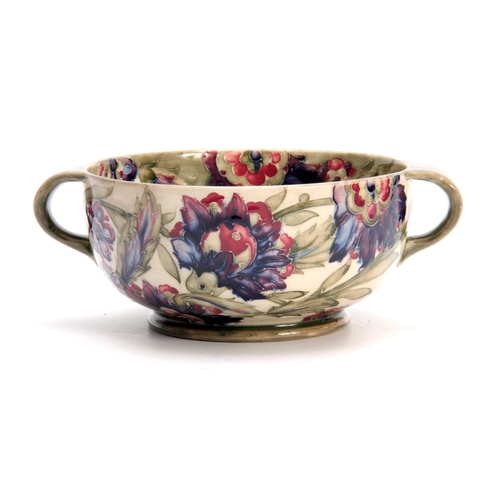 38 - A WILLIAM MOORCROFT BURSLEM FOOTED TWO-HANDLED BOWL with colourful tube lined flowerhead and leaf sp...
