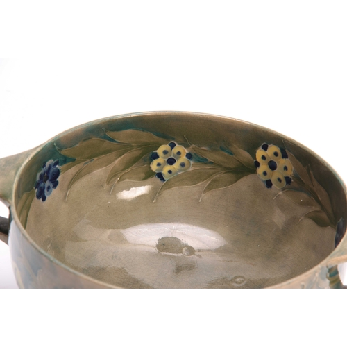 39 - A WILLIAM MOORCROFT BURSLEM FOOTED TWO-HANDLED BOWL with flowerhead and leaf spray decoration on a s...