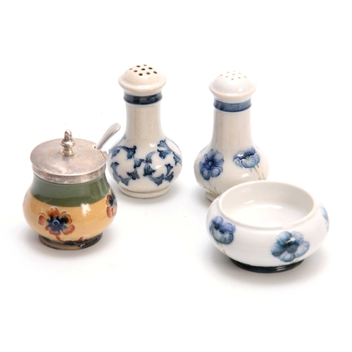 46 - A MACINTYRE BURSLEM FLORIAN WARE MATCHED THREE PIECE CONDIMENT SET comprising a pair of pepperettes ...