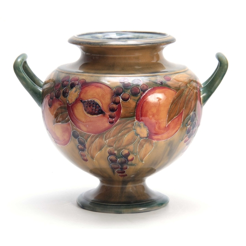 49 - AN EARLY WILLIAM MOORCROFT LARGE TWO-HANDLED FOOTED BULBOUS VASE tube lined and decorated with a con...