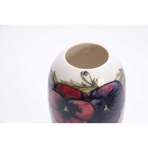 50 - A MOORCROFT TAPERING SHOULDERED VASE decorated with leafing different coloured pansy sprays on a cre...