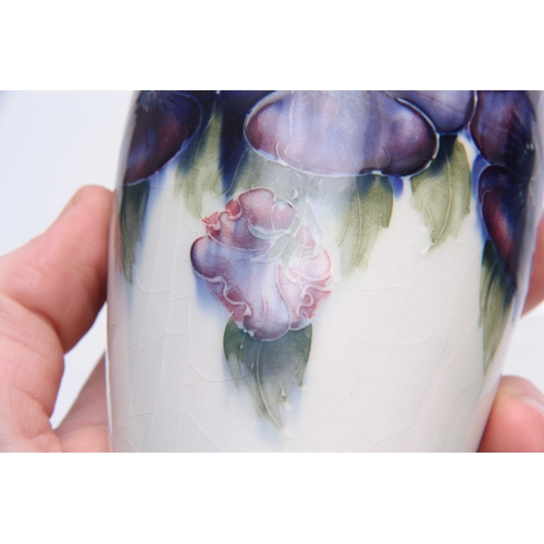 57 - A WILLIAM MOORCROFT TAPERING SHOULDERED VASE decorated with all round leafing pansy sprays on a neut...