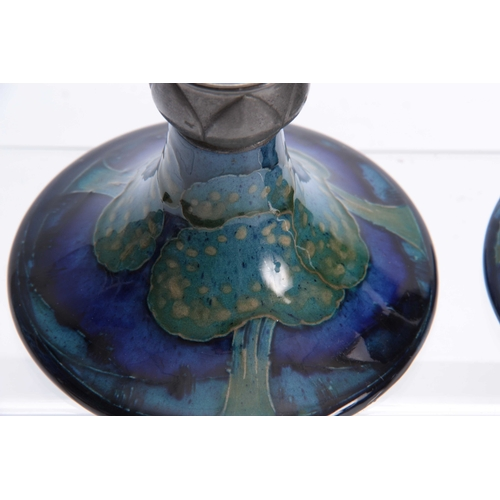59 - A PAIR OF MOORCROFT MOONLIT BLUE TAPERING CIRCULAR BASE CANDLESTICKS WITH TUDIC PEWTER SCONCES 10cm ...