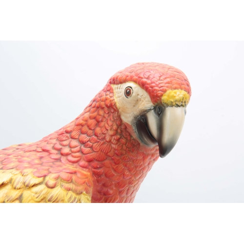 115 - AN EARLY 20TH CENTURY ITALIAN POTTERY MACAW PARROT perched on blossoming tree - 46cm high...
