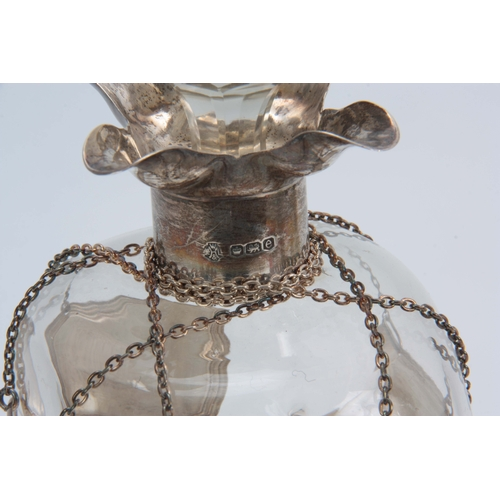20 - A GEORGE V SILVER MOUNTED SPIRIT DECANTER AND STOPPER with quatrefoil pouring lips and pinched clear...