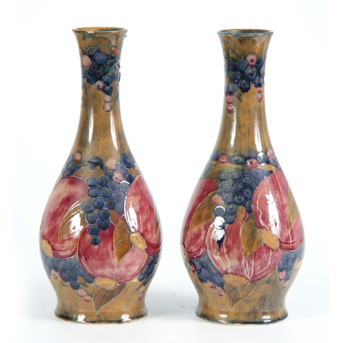 44 - A PAIR OF 20TH CENTURY MOORCROFT VASES decorated with pomegranates and grapes bearing green signatur...