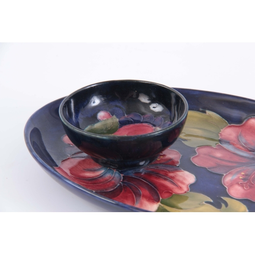 45 - A MID 20TH CENTURY WALTER MOORCROFT OVAL HIBISCUS PLATE on a blue ground  23cm by 15.5cm TOGETHER WI...