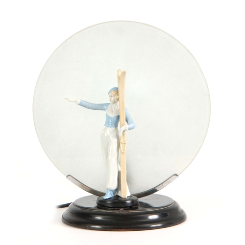 64 - A 1930'S ART DECO CONTINENTAL LAMP mounted with a porcelain figure of a skier having a circular fros...