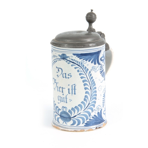 87 - AN 18TH CENTURY GERMAN BLUE AND WHITE PEWTER MOUNTED DELFT TANKARD bearing inscription 'Das bie ift ...